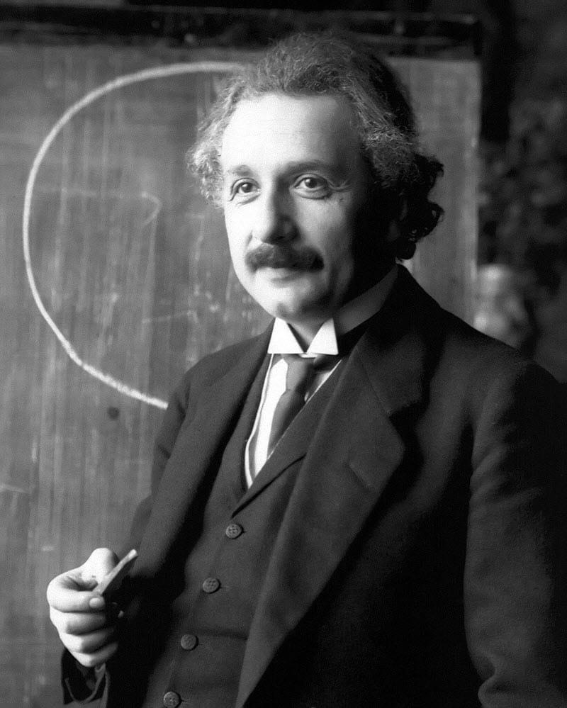 Albert Einstein standing in front of a chalkboard