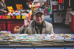 Man browsing books outdoors, holding up thumb and forefinger together