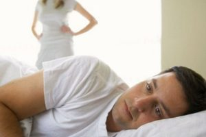 Man lying in bed facing away from disappointed woman