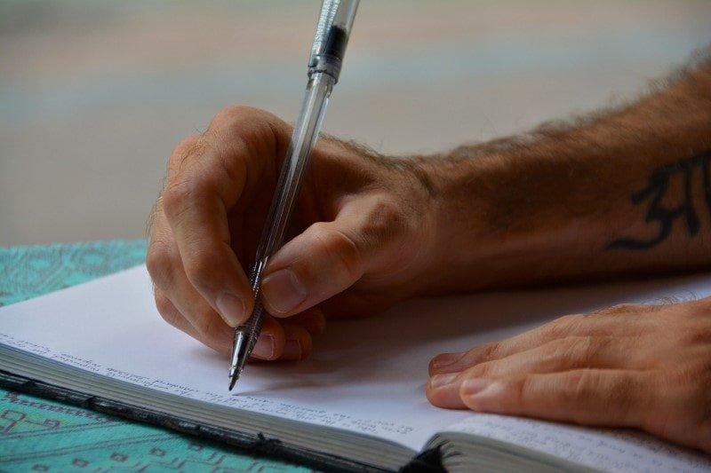 Closeup of man writing in a journal