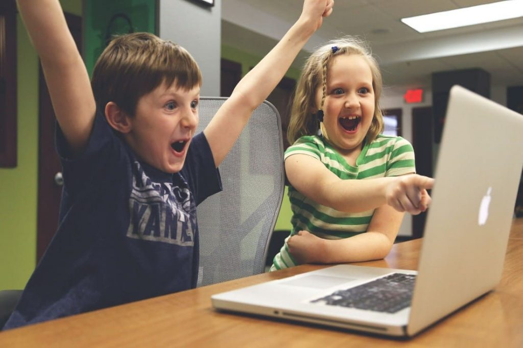 Happy children looking at a laptop