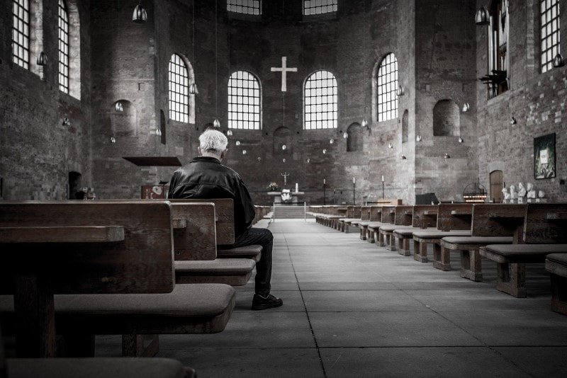 Older man sitting in the back of a church and praying