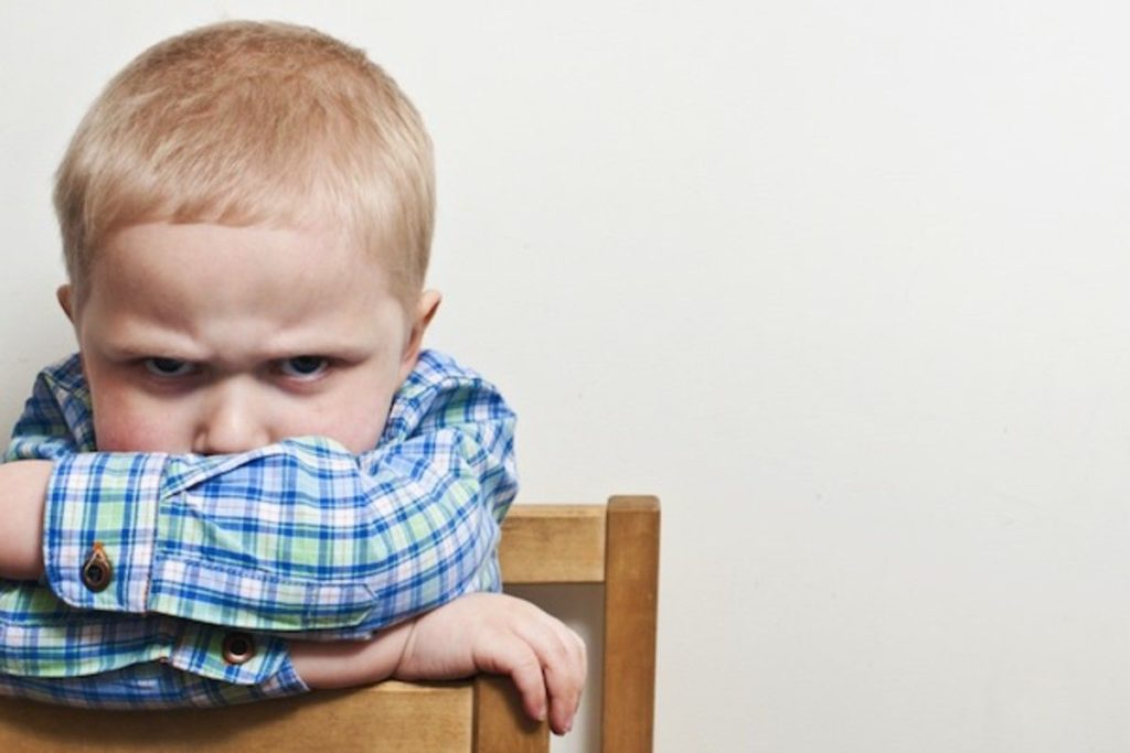 Unhappy child with chin on crossed arms