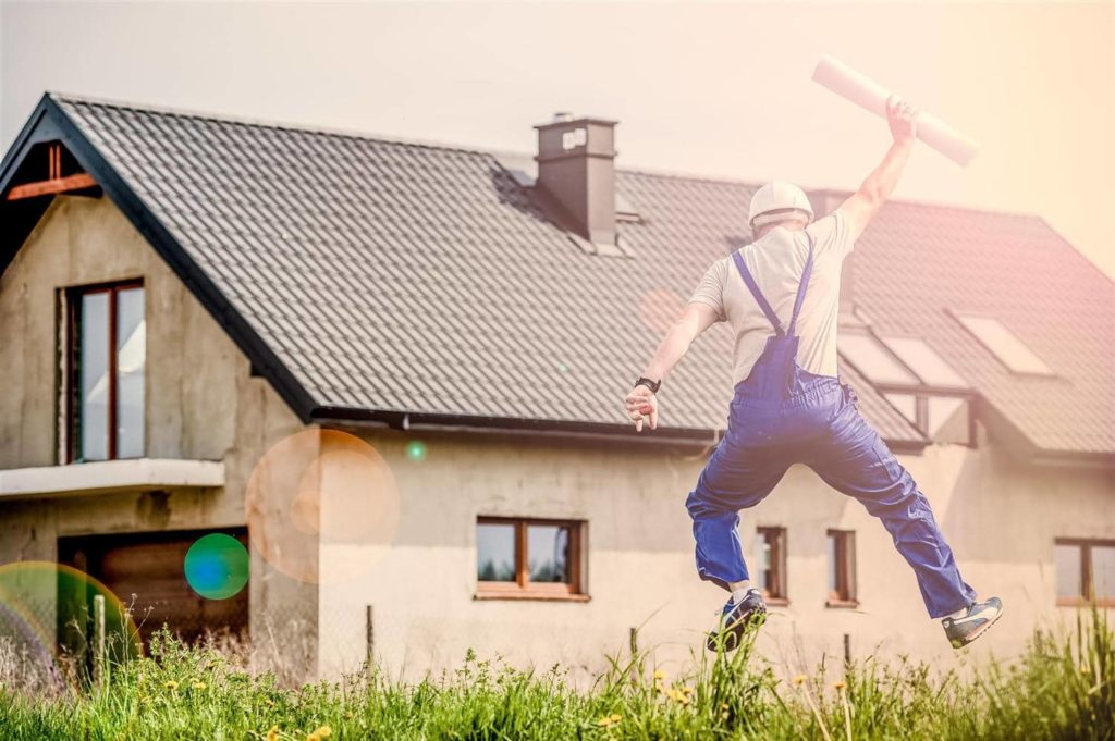 Man in overalls holding architecture plans jumping in the air