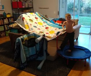 "Picture of a child in front of a ""fort"" built with blankets and furniture"